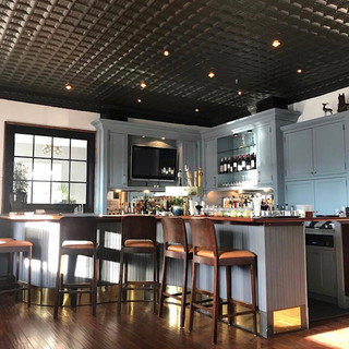 image of small, serpentine shaped bar with wood and orange leather barstools, light blue cabinetry, black tin ceilings, and a gridded window with natural light shining through