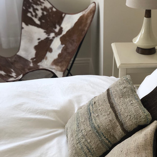 close up image of guestroom containing a cowhide butterfly chair, turkish pillows, mid-century modern style lamp, crisp white bedding
