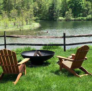2 adirondack chairs, firepit, and lake in the background