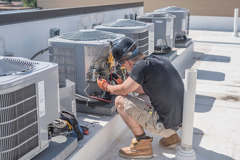 Hvac tech on roof top checking a condens