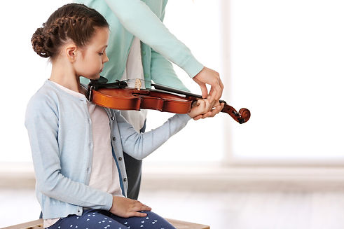 Small girl learning play violin with tea