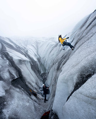 WOMAN IN YELLOW JACKET ICE CLIMBING ON A GLACIER