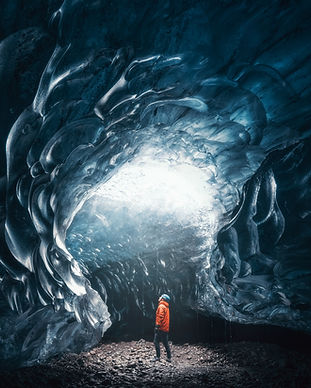 MAN STANDING INSIDE ICE CAVE IN ICELAND.