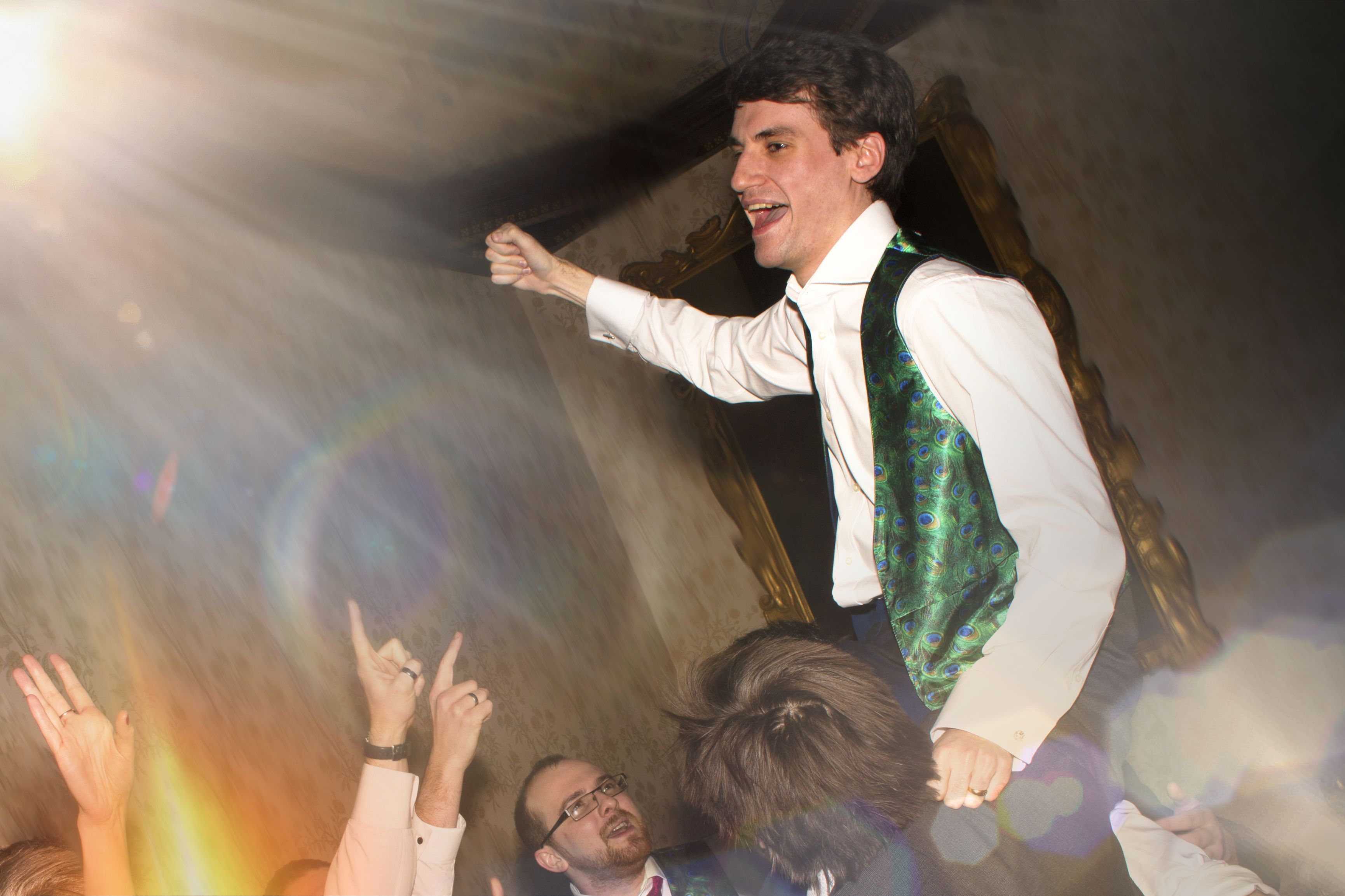 Groom lifted on guests shoulders