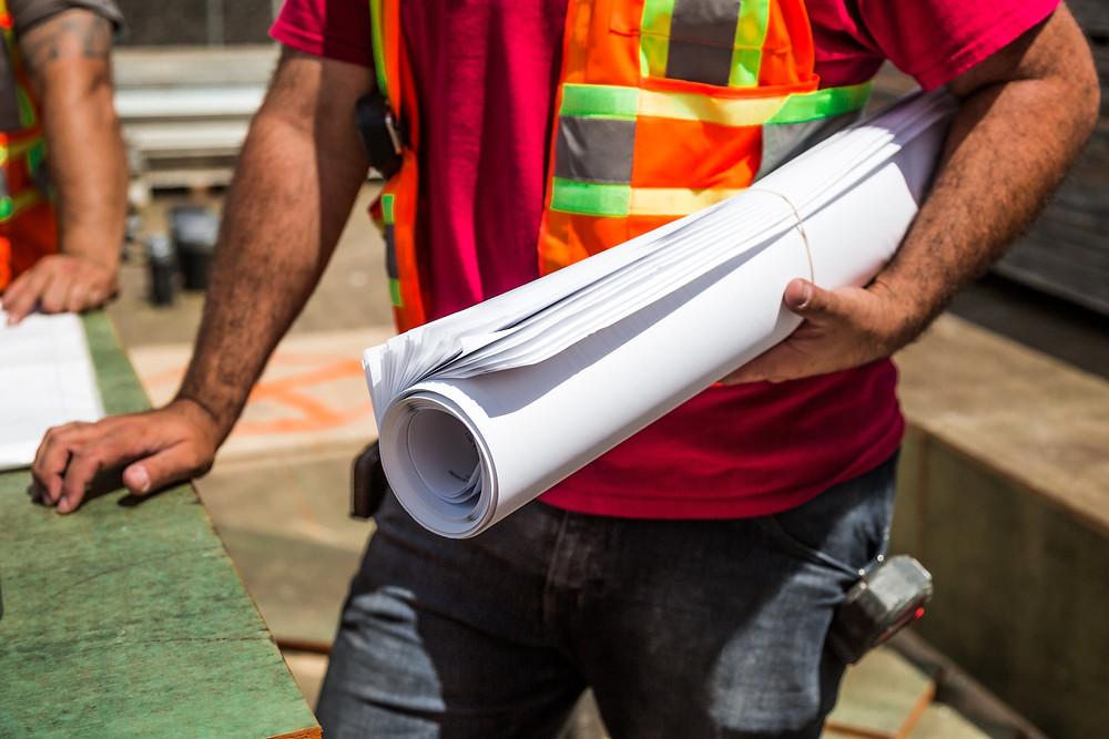 Un travailleur de la construction tient des plans.