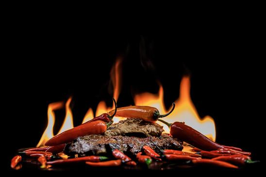 Kepti šonkauliukai, ugnies fone