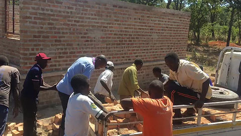 Chibombo community members transporting bricks onsite for the completion of 1x3 classroom block as part of their 25% material contribution.