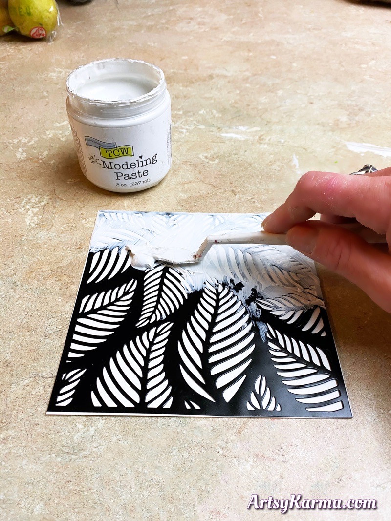 Spread texture paste through a stencil to create artist trading card backgrounds