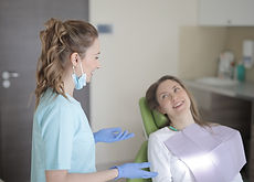 cheerful-young-female-dentist-talking-wi