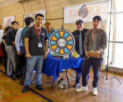 Teens and an adult volunteer stand next to a colorful spinning wheel