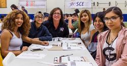 Teens sit around a table with an adult teacher