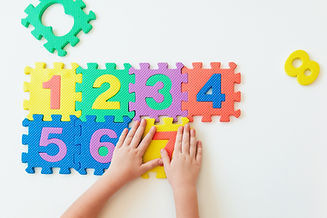childs-hands-playing-with-numbers-learni