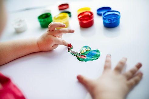 kid-hands-start-painting-at-the-table-wi