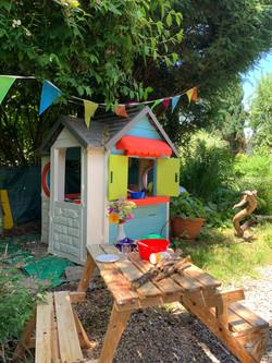 Das farbenfrohe Spielhaus steht schön eingebettet mitten im Zaubergarte...