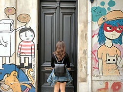Eine Frau steht vor eine Tür neben Street Art