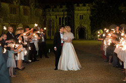 Bride and Groom in a magical evening moment with all the guests at the main entrance of Athelhampton