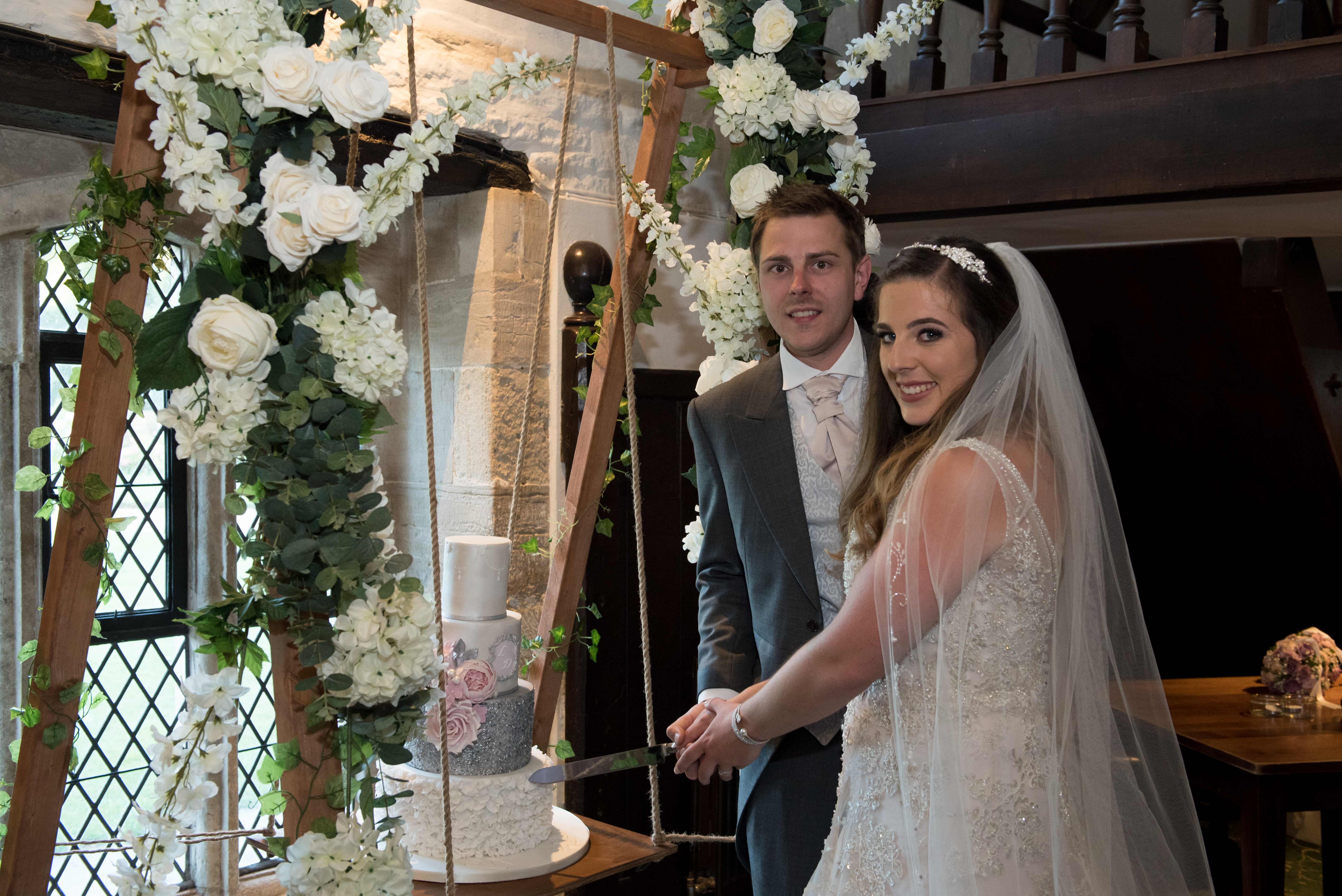 Bride and Groom Cutting the Wedding Cake in the Long Hall at Athelhampton
