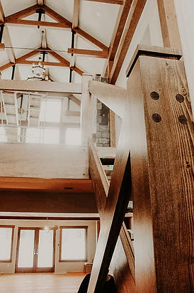 Interior of a rustic home with timber frame accents. wood stairs and aulte ceiling / roof.