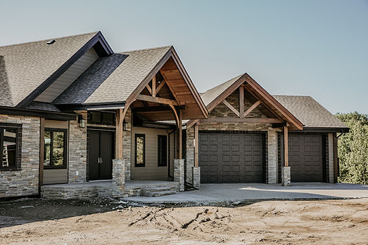 front view of a rustic home with timber frame accents on the front entrance and the garage.