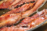 Whole30 bacon frying in a pan <img>