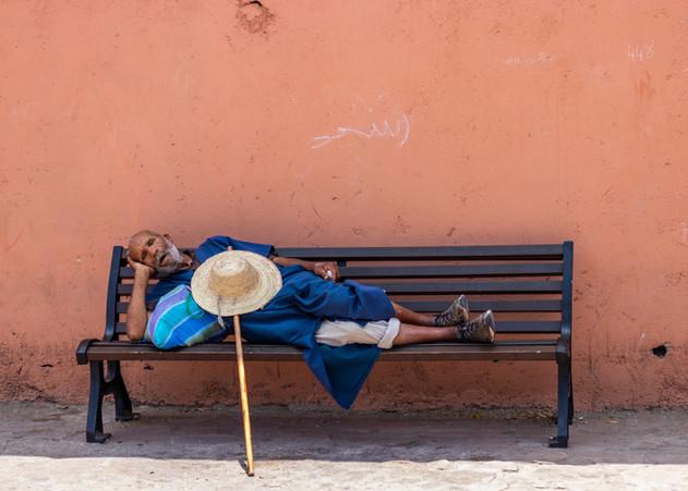 sleeping man marrakech walking stick hat morocco travel photography