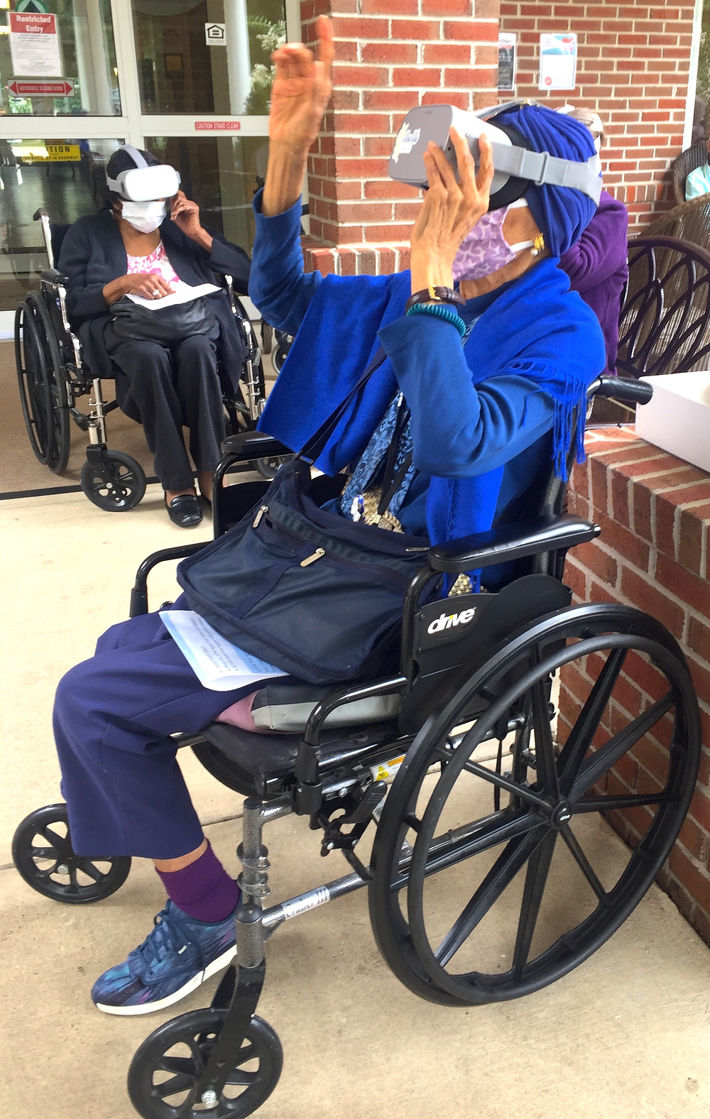 Retired people use Viva Vita virtual reality to travel around the world without leaving their wheelchair. Two women wear virtual reality headsets.