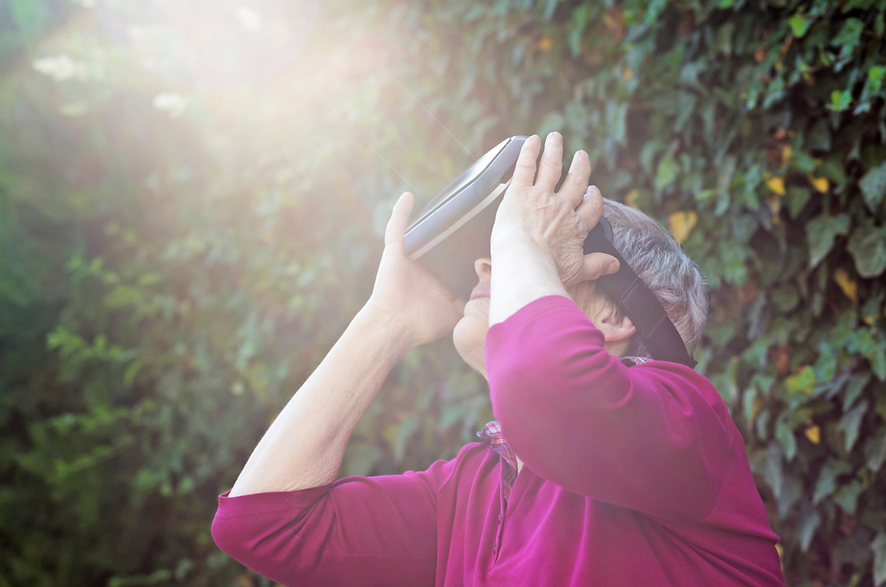 Senior wearing a VR headset outdoors, looking at the sky
