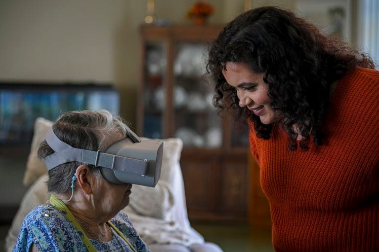 Nursing home resident wears Viva Vita virtual reality goggles while caregiver smiles and assists with guiding the virtual tour.