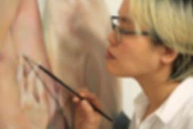 Man Yu pintando obra para el proyecto Traje Humano