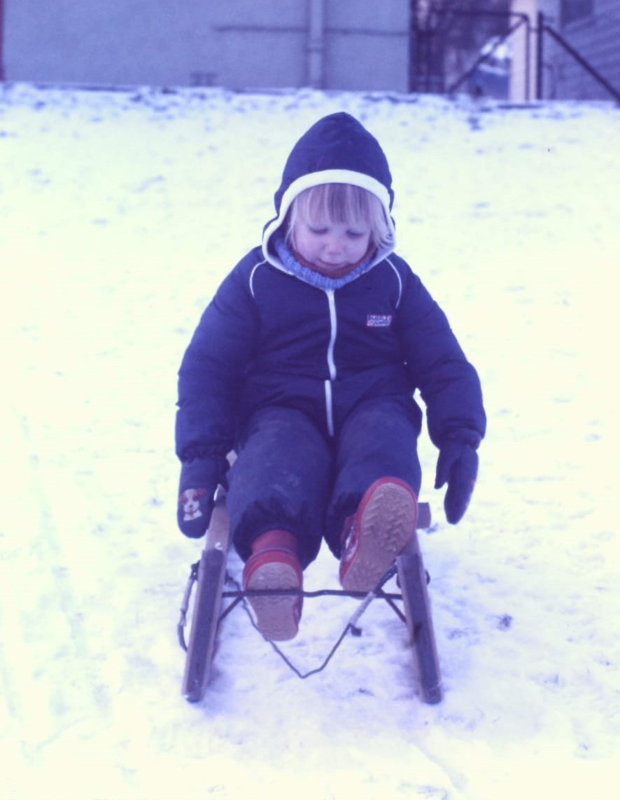 Young blond girl on a sled in the snow