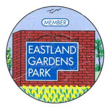 A Circular logo of our Eastland Gardens entryway with small yellow flowers, green trees and grass.