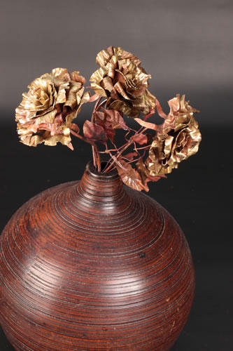 3 copper roses in African wooden bowl