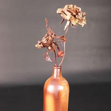 2 brass roses in ceramic gin bottle
