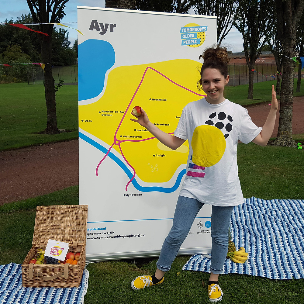 Team member Rachel standing in front of a colourful map of Ayr in the park