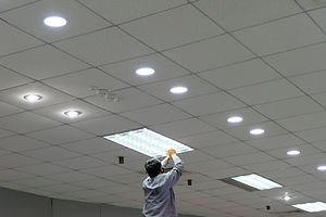 Maintenance man changing light bulbs in