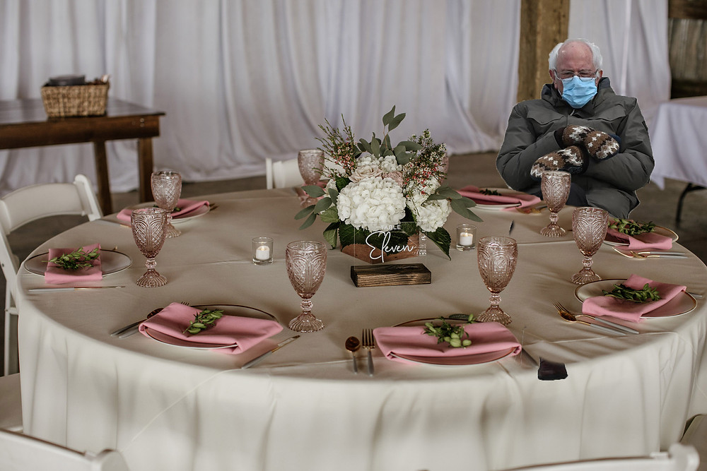 Bernie sits socially-distanced and wears a mask at a wedding reception table.
