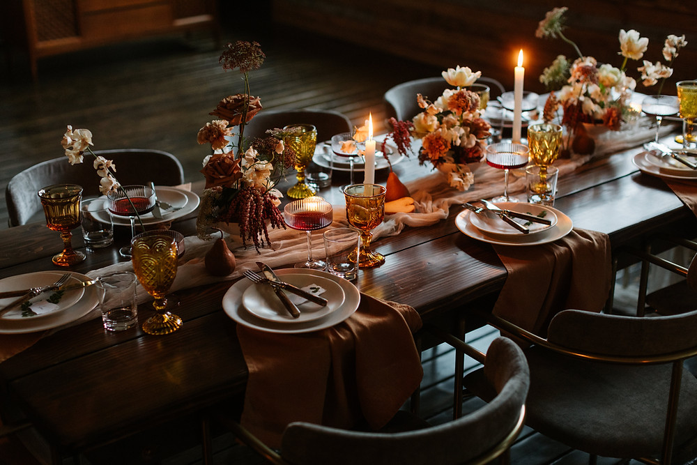A moody wedding reception table lit with candles and decorated with wildflowers, amber glasses.