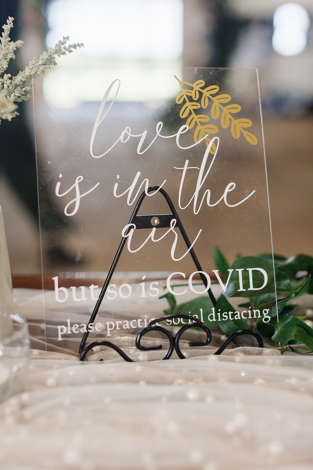 """an image of a sign that says """"love is in the air but so is COVID-19 so please practice social distancing"""""""