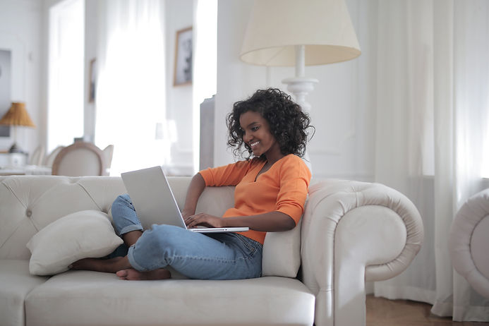 woman-sitting-on-white-couch-using-lapto