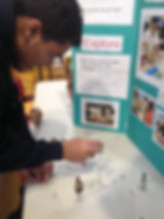 Student exploring with clips in front of STEM display