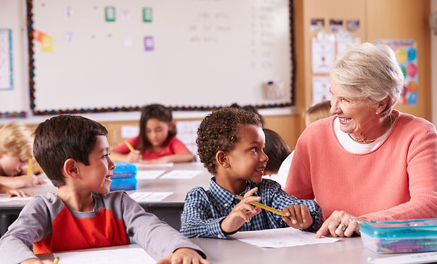 senior-teacher-sitting-with-elementary-s