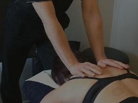 Masseur massaging a client's back