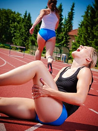 Athlete in pain holding hamstring