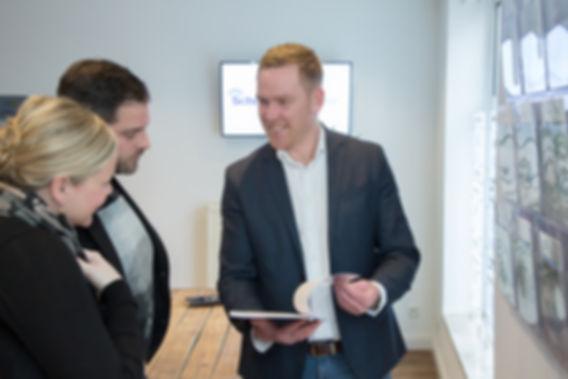 André Schurillis berät Kunden und zeigt Bewertung einer Immobilie