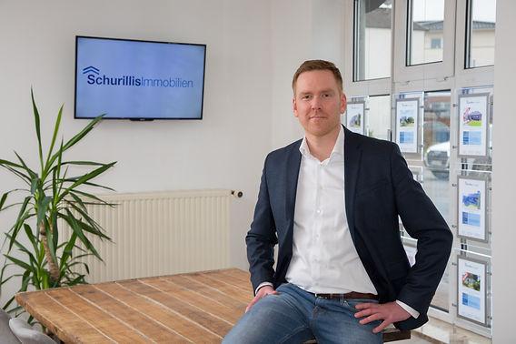 André Schurillis sitzt auf Tisch im Büro