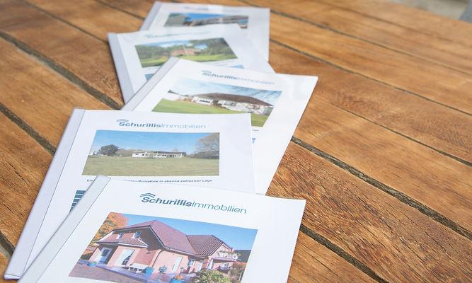 Exposés Schurillis Immobilien liegen auf Tisch