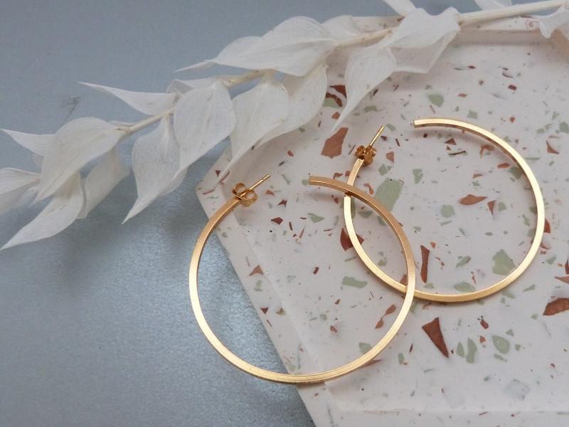 Gold plated hoop earrings on a terazzo trinket tray