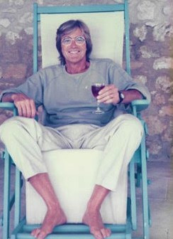 A smiling young man, sitting outside, holding a glass of red wine.