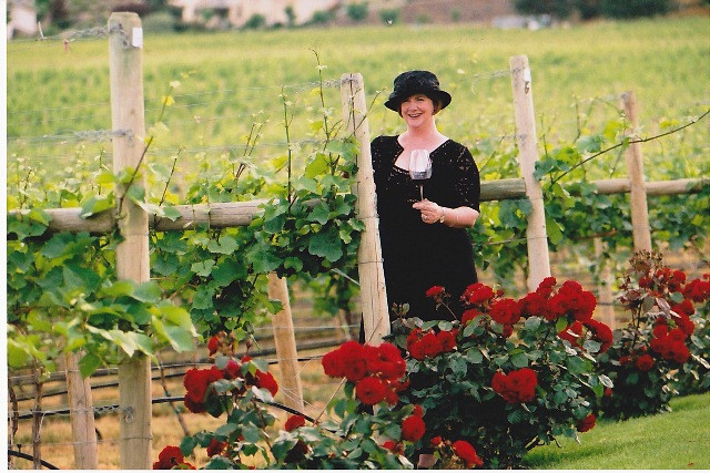 Woman holding glass of wine in vineyard