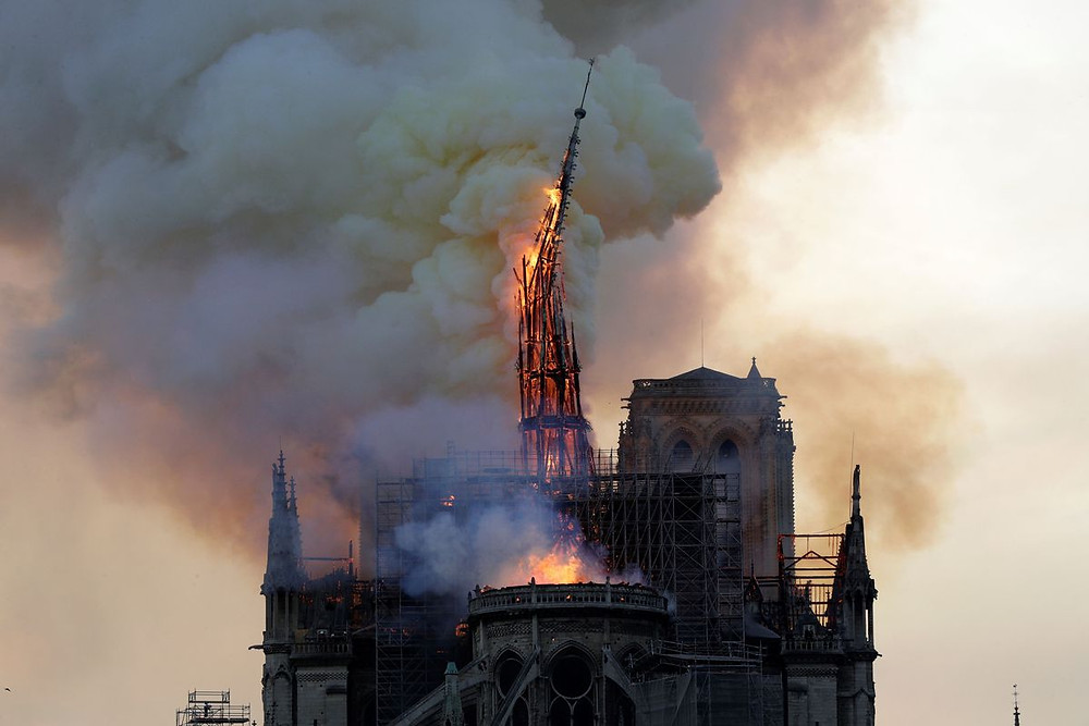 As fire burns, the central spire of Notre Dame Cathedral in Paris collapses. (Getty)